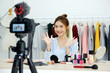 Young asian woman beauty blogger showing how to make up video tutorial recording by camera, vlog concept, fashion people and technology communication