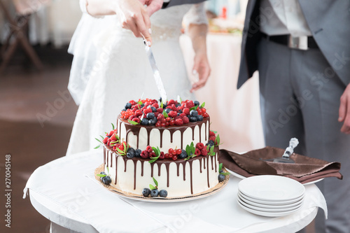 Stampa su Tela Bride and groom cut beautiful rustic wedding cake on wedding banquet