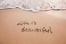Life Is Beautiful, Positive Thinking Concept. Inspirational Quote Written On Sand.