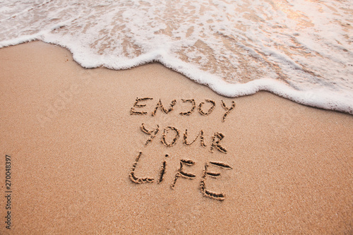 Obraz Enjoy your life, happiness concept, positive thinking, inspirational quote written on sand beach. - fototapety do salonu
