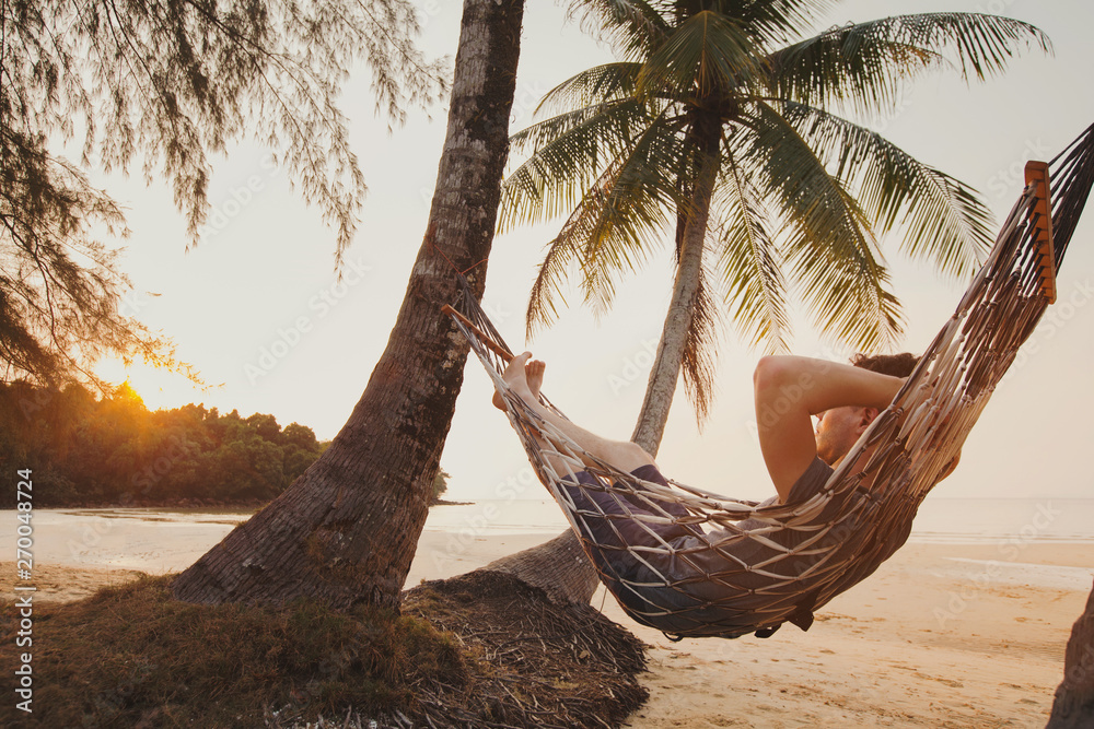Fototapety, obrazy: tourist relaxing in hammock on tropical beach with coconut palm trees, relaxation and leisure tourism