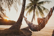 canvas print picture - tourist relaxing in hammock on tropical beach with coconut palm trees, relaxation and leisure tourism