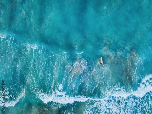 Valokuva aerial top down view of surfer with surf board in ocean wave from drone