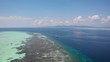 Beautiful clear blue waters in Balabac, Palawan, drone shot of the Reef around Onuk Island and a boat in the background