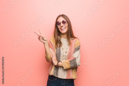 Young hippie woman on pink background doing a gesture of victory Wallpaper Mural