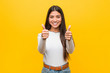 Young pretty arab woman against a yellow background with thumbs ups, cheers about something, support and respect concept.