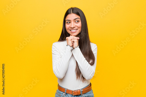 Pinturas sobre lienzo  Young pretty arab woman against a yellow background keeps hands under chin, is looking happily aside
