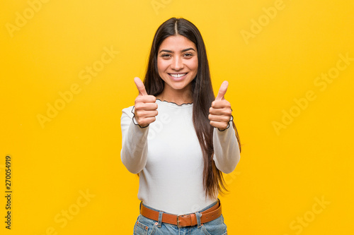 Fotografiet  Young pretty arab woman against a yellow background with thumbs ups, cheers about something, support and respect concept