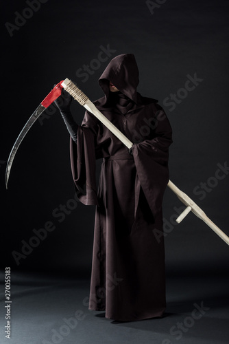 Fotografía full length view of woman in death costume holding scythe on black