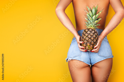 Photo Young woman holding a pineapple in her hand.