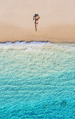 Fototapeta Morze Aerial view of a girl on the beach. Vacation and adventure. Beach and turquoise water. Top view from drone at beach, azure sea and relax girl. Travel and relax - image