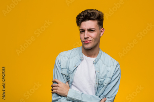 Photo  Young handsome student wearing a denim shirt unhappy looking in camera with sarcastic expression
