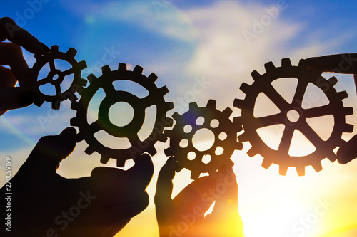 Fototapety, obrazy: gears in the hands of people against the blue sky. mechanism, interaction, teamwork.