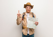 Young Redhead Explorer Man Showing Number One. Holding A Map.