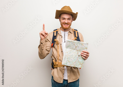 Cuadros en Lienzo Young redhead explorer man showing number one. Holding a map.