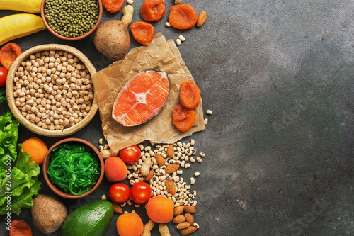 Foods rich in potassium, salmon, legumes, vegetables, fruits on a dark background. Healthy food concept,avitaminosis prevention. Top view, flat lay,copy space. - 270063559