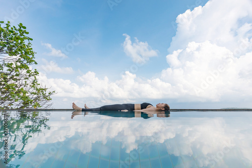 Fotomural  Vacation of Beautiful Attractive Asian woman relaxing in yoga Savasana pose on t