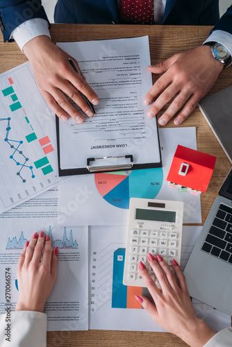 partial view of customer reading loan agreement and businesswoman using calculator while sitting at workplace near laptop, house model, graphs and charts - 270066574