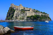 Leinwandbild Motiv Aragonese Castle with boat in the blue waters off the island of Ischia, Italy