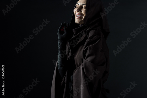 laughing woman in death costume holding dice isolated on black Tablou Canvas