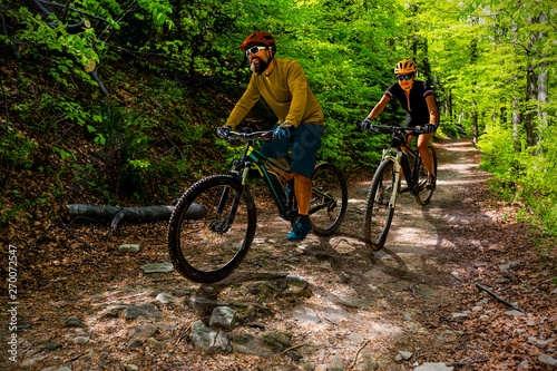 fototapeta na drzwi i meble Cycling woman and man at Beskidy mountains autumn forest landscape. Couple riding MTB enduro track. Outdoor sport activity.