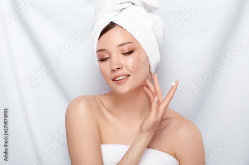 Fototapeta attractive woman in bath towel applying cream on her face isolated on white obraz na płótnie