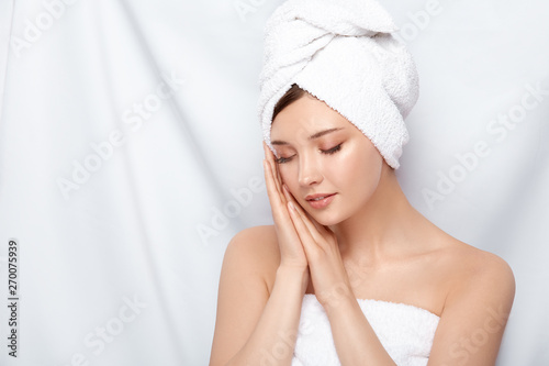 Fototapeta young and beautiful female in bath towel holding her hands near face with her eyes closed, pretty woman after treatment procedures obraz na płótnie