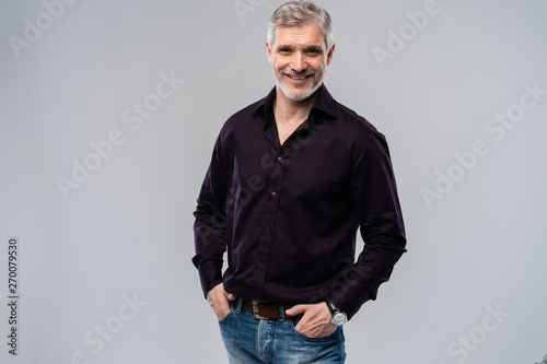 Fotomural  Cheerful man of middle age against white background, wearing jeans and black shirt, mid shot