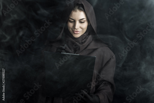 woman in death costume holding clipboard on black Tablou Canvas