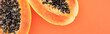 canvas print picture - panoramic shot of ripe papaya halves with black seeds isolated on orange