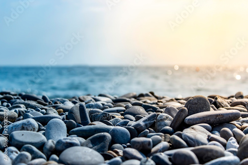 Fotografiet  Sea stones and waves on the beach. Summer background.