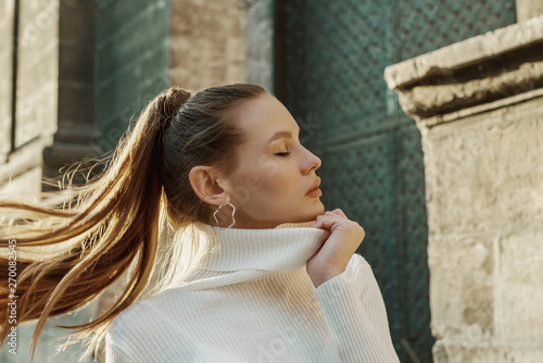 Foto Fashionable woman with long hair in ponytail hairstyle wearing trendy hoop earrings, white turtleneck sweater, posing in street of European city