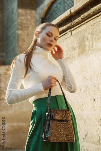 Fashionable woman posing in street of city. Model wearing white turtleneck sweater, green high waisted trousers, holding reptile textured handbag Wall mural