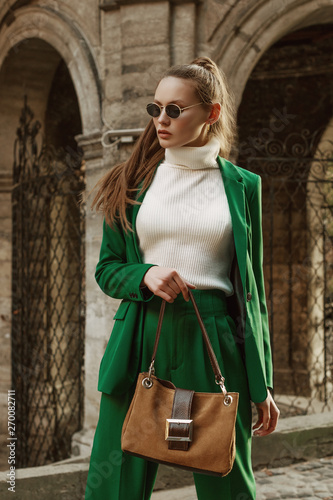 Fashionable woman posing in street of city. Model wearing white turtleneck sweater, green suit: blazer, high waisted trousers, sunglasses, holding reptile brown suede handbag Wall mural