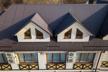 Close-up Aerial View Of Building Attic Rooms Exterior On Metal Shingle Roof, Stucco Walls And Plastic Windows.
