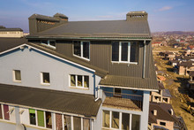 Aerial View Of Attic Annex Room Exterior With Plastic Windows, Roof And Walls Covered With Brown Metal Decorative Siding Planks, New Gutter System On Top Of Apartment Building.