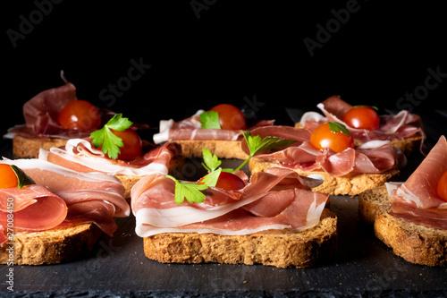 Foto jamón serrano sobre pan tostado con tomate cherry y perejil, en clave oscura y p