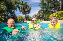 A Young Boy And His Grandparents Splashing, Playing, And Having Fun At A Water Park. Smiling And Having A Great Summer Vacation.