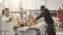 Committed To Quality. Committed To You. Carpenter Cutting Wood On Electric Saw