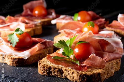 Fotomural jamón serrano sobre pan tostado con tomate cherry y perejil, en clave oscura y p