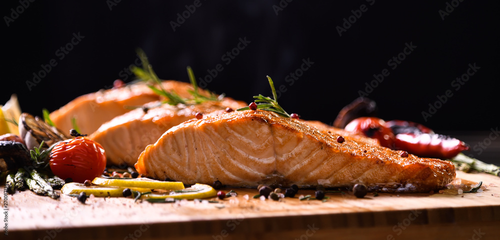 Grilled salmon fish and various vegetables on wooden table on black background