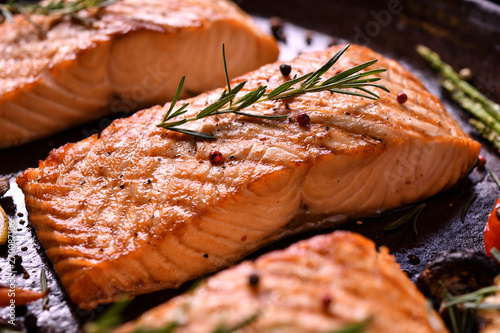 Fotografia Grilled salmon fish with various vegetables on pan on the flaming grill