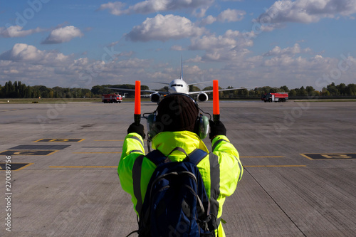 Photo A supervisor helps at the aircraft parking at the airport