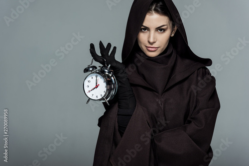 Fotografie, Tablou woman in death costume holding alarm clock isolated on grey