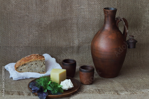 Fotografie, Obraz Hard and soft cheese with greens on round clay plate, jug for wine, cup and bread on white cloth on homespun rough background
