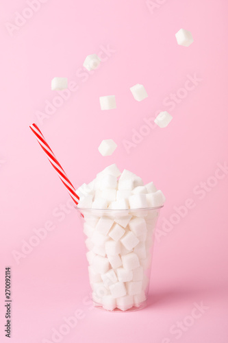Pinturas sobre lienzo  Sugar cubes falling into glass on pink background Unhealthy diet concept