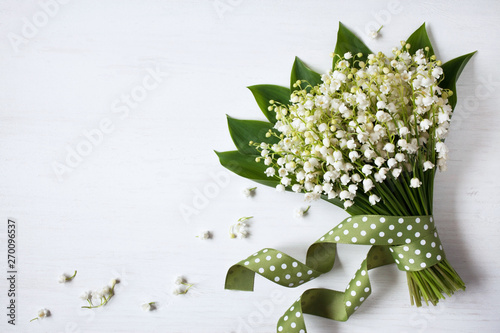 Deurstickers Lelietje van dalen A bouquet of lily of the valley on a wooden background