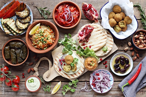 Canvas Middle eastern, arabic or mediterranean appetizers table concept with falafel, pita flatbread, bulgur and tomato salads, grilled vegetables, stuffed grape leaves,olives and nuts