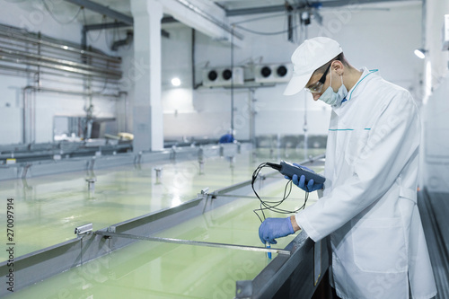 Fotomural man in a white robe and a cap make an inspection of dairy products