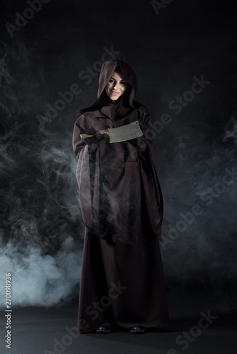 full length view of woman in death costume holding cleaver in smoke on black Fototapet